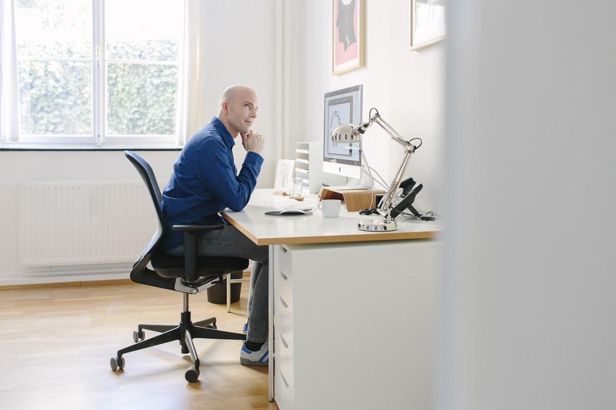 Modernes Portraitfoto eines Mannes, der am Schreibtisch vor seinem Computer sitzt