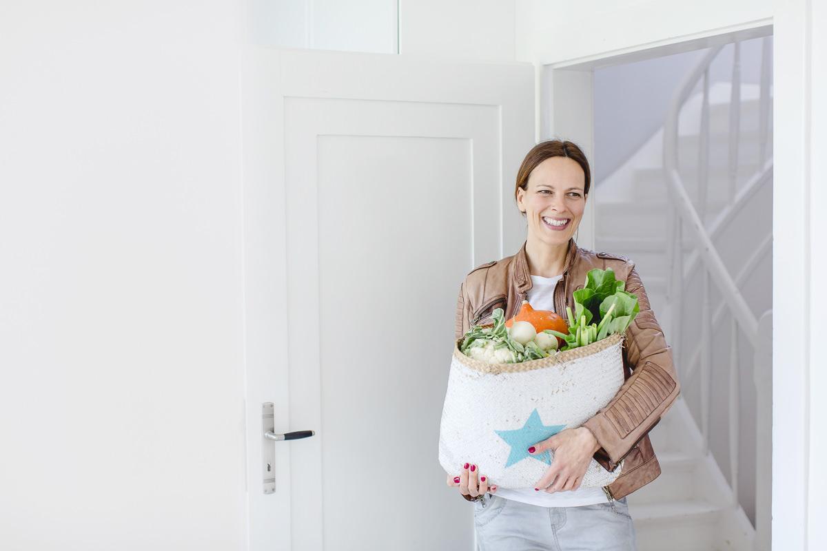 freundliches Portraitfoto einer Foodbloggerin mit einer Einkaufstasche voller Lebensmittel