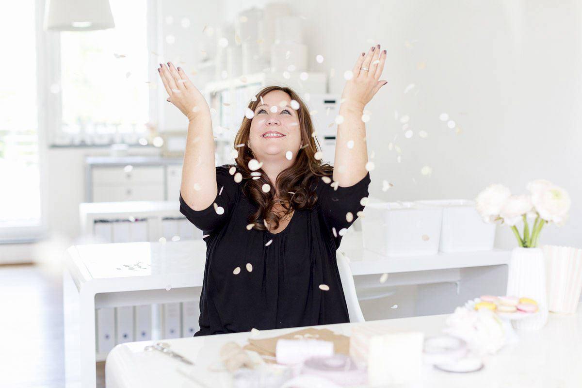authentisches Businessportrait einer Hochzeitsplanerin, die Konfetti in die Luft wirft