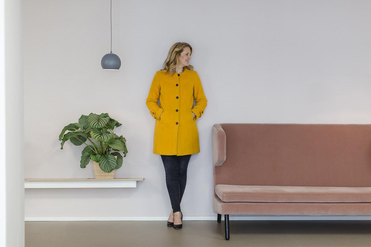 modernes businessfoto einer unternehmerin, die entspanntan einer Wand lehnt