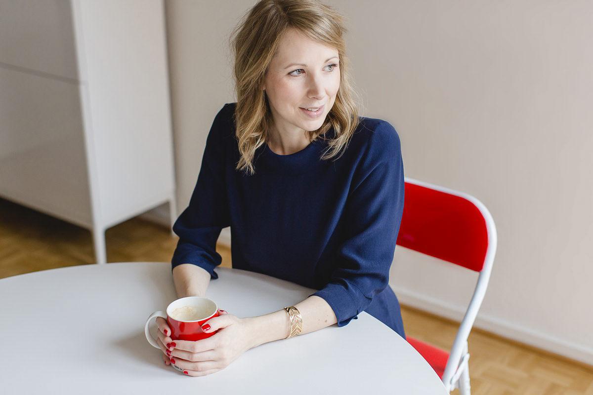 modernes Businessfoto einer jungen Frau, die mit einer Tasse Kaffee am Tisch sitzt