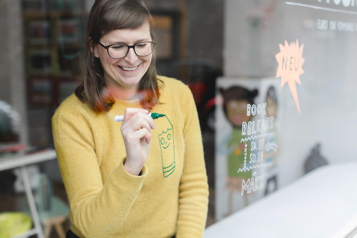 modernes Businessportrait einer Frau, die etwas an ihr Schaufenster schreibt