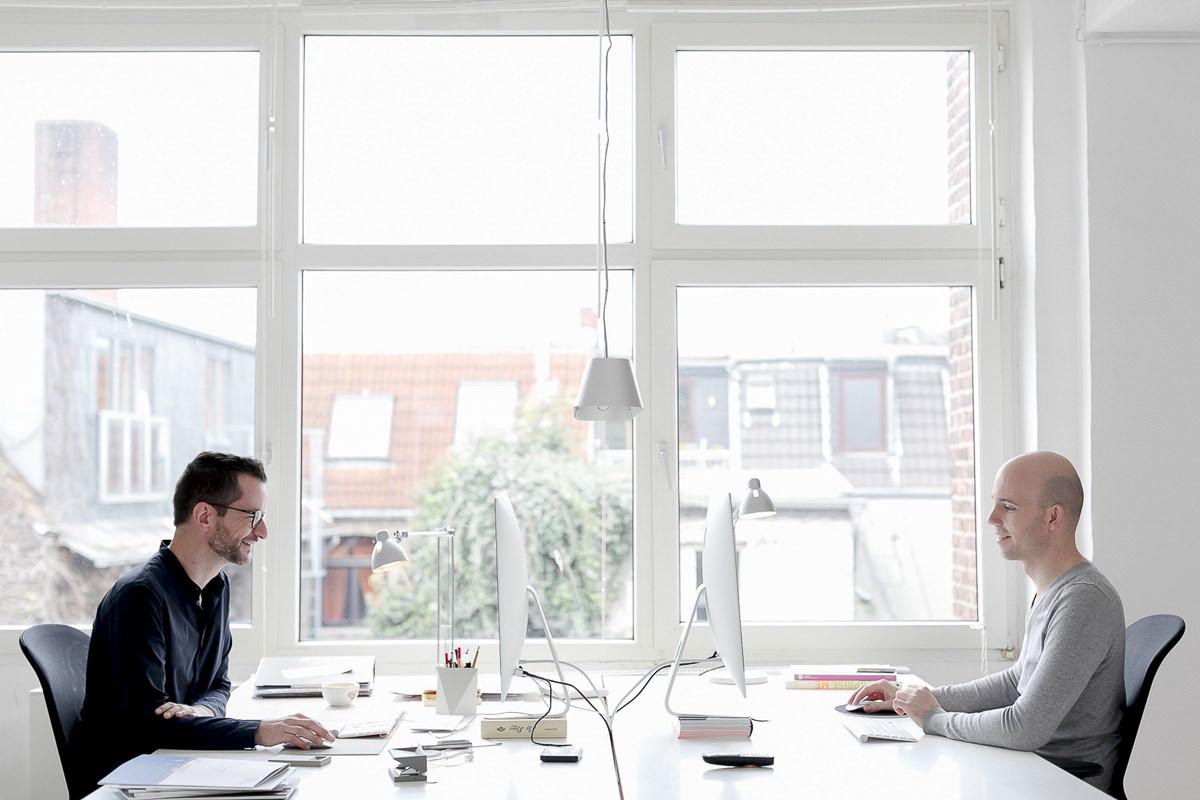 Portraitfoto von 2 Agenturinhabern am Schreibtisch