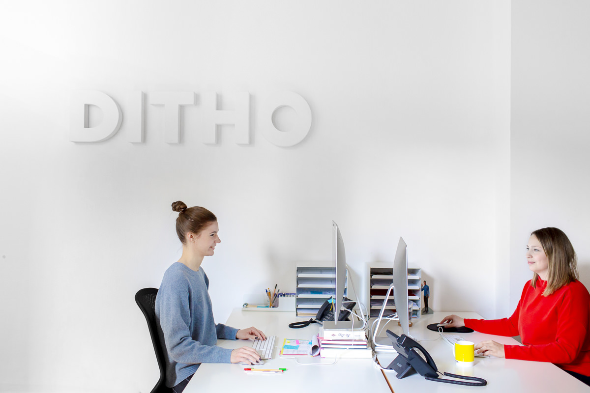 Portraitfoto von 2 Agenturmitarbeiterinnen vor ihren Computern