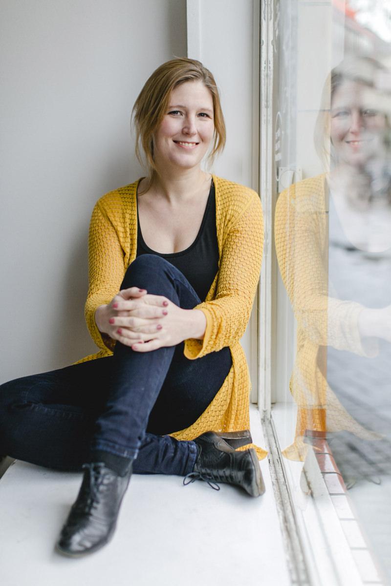 Natürliches Portraitfoto einer Frau am Fenster fotografiert von Hanna Witte