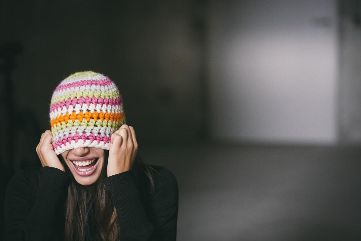 lustiges Portraitfoto einer Frau, die sich ihre Wollmütze über die Augen zieht