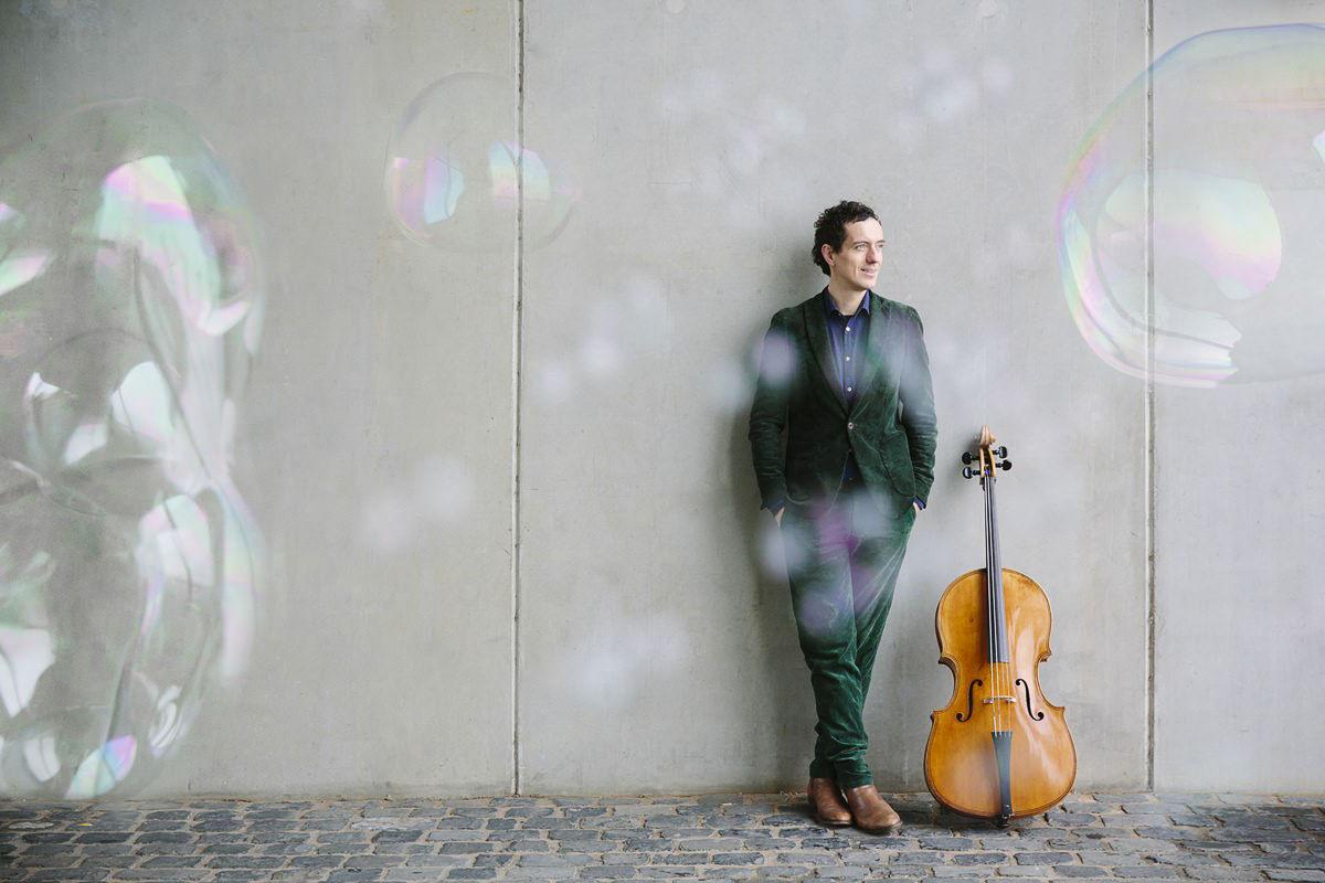 Künstlerportrait eines Cello Spielers mit herumfliegenden Seifenblasen