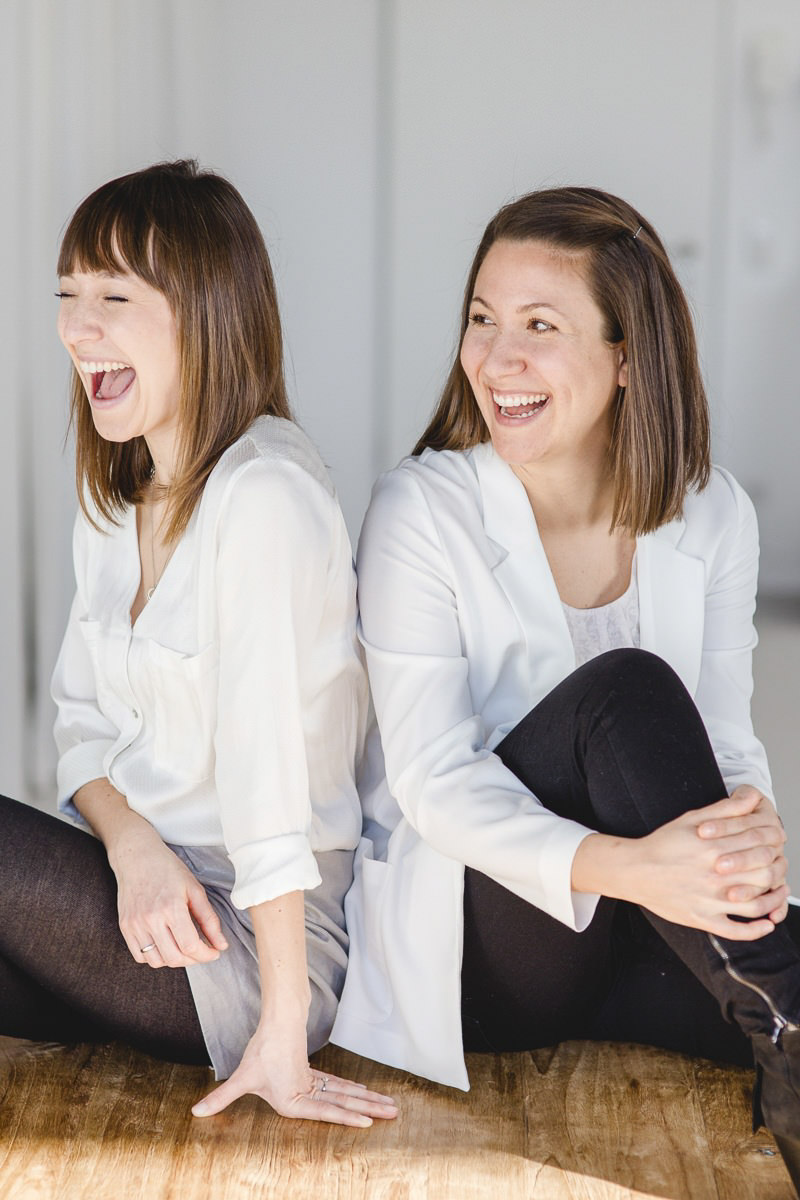 Modernes Business Portrait von 2 jungen Frauen, die ausgelassen lachen
