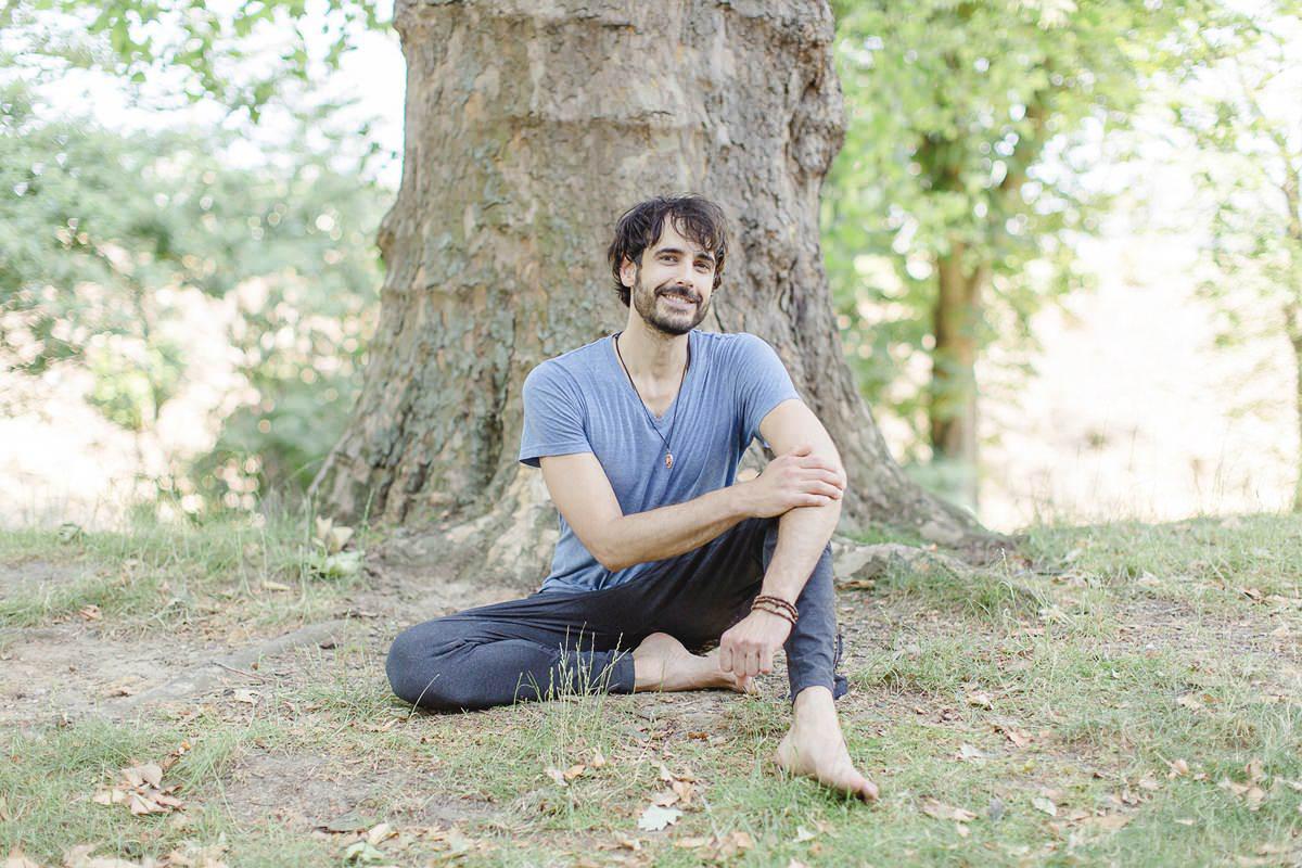 natürliches Portraitfoto eines Yoga Lehrers vor einem Baum