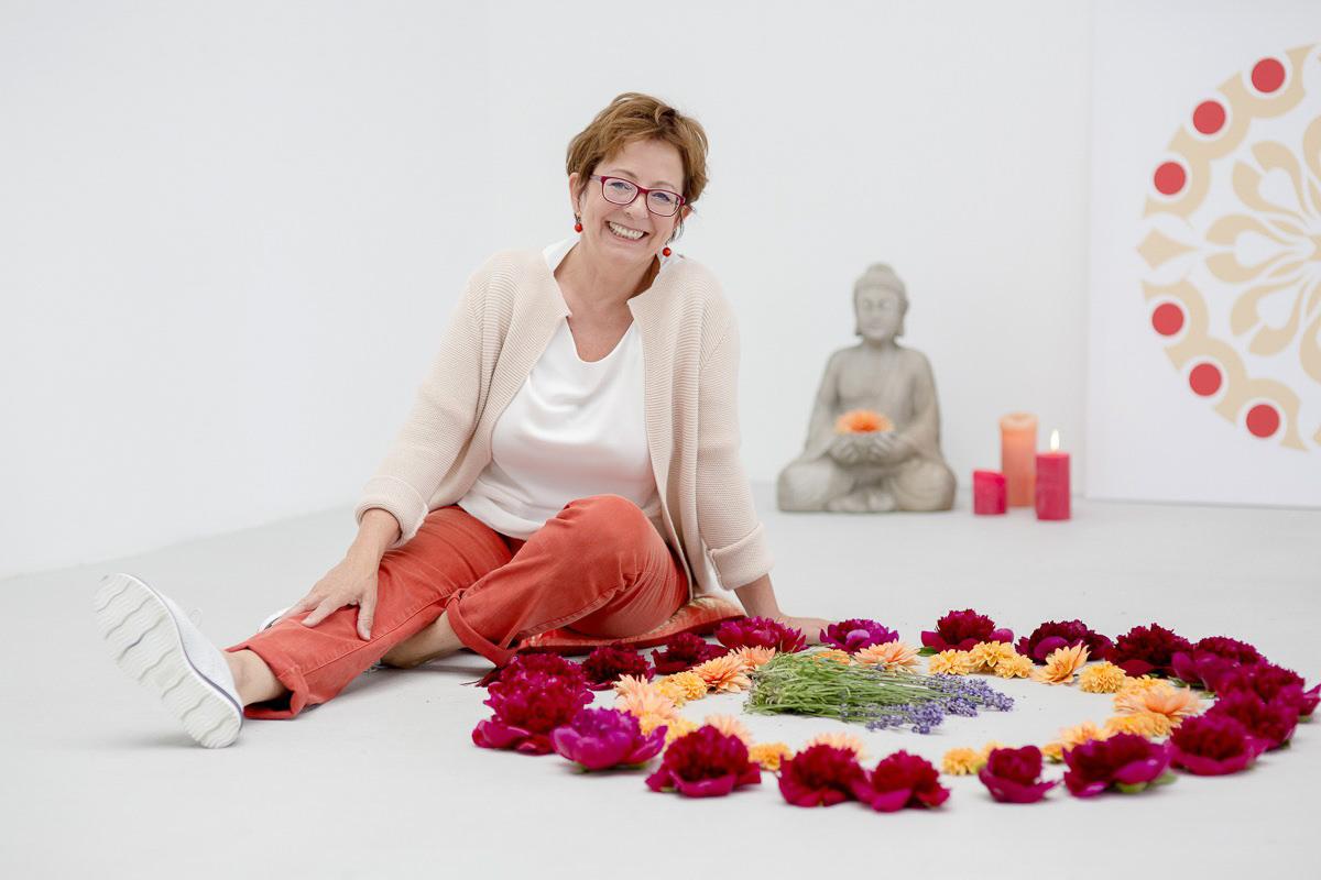 Portraitfoto einer Architektin und Feng Shui Beraterin, die neben einem bunten Blütenkreis sitzt