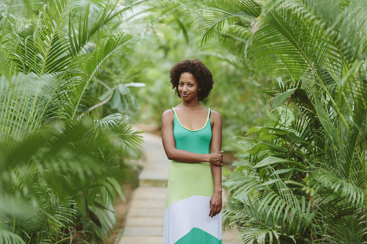 natürliches Portraitfoto einer Frau zwischen vielen grünen Blättern