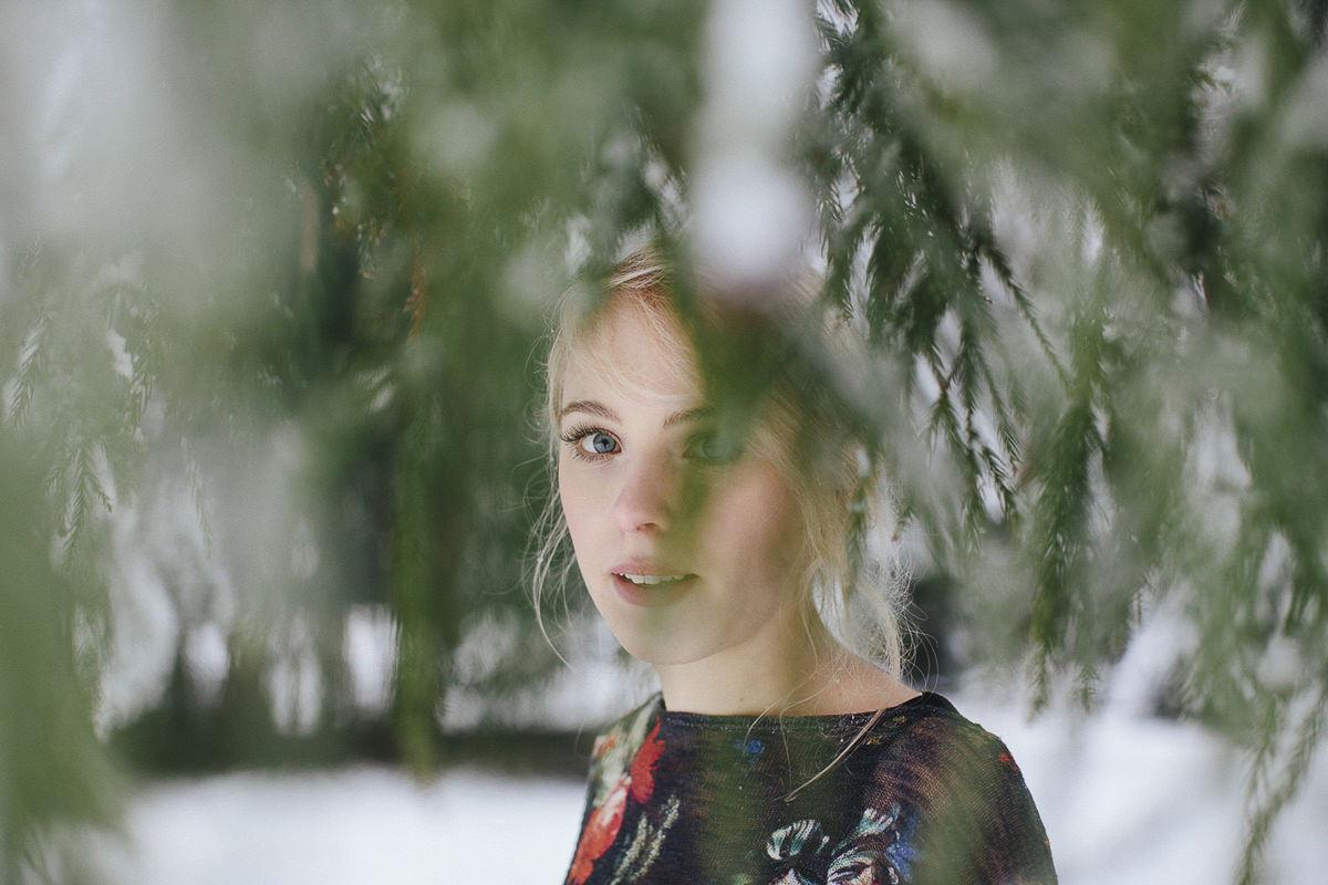 besonderes portraitfoto einer jungen Frau zwischen Bäumen im Schnee