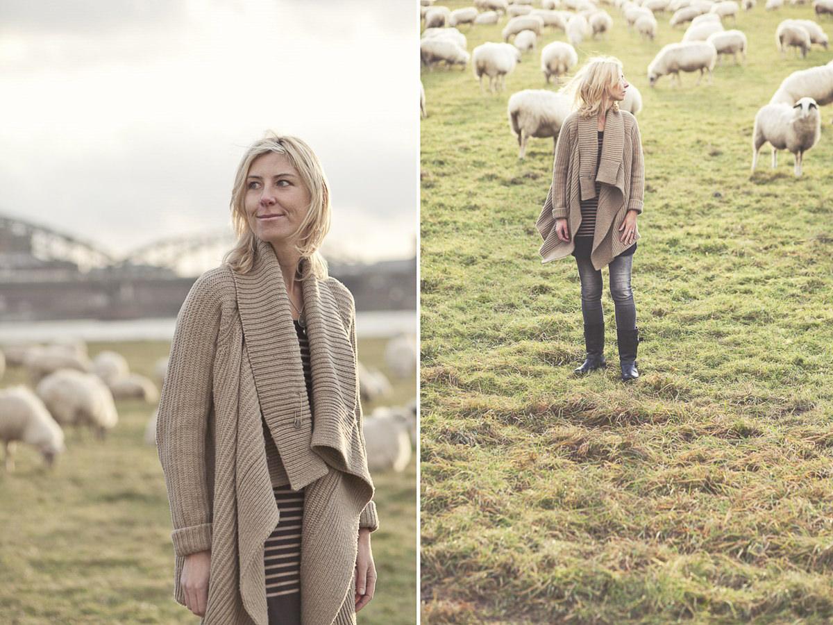 natürliches Portraitfoto einer Frau zwischen Schafen