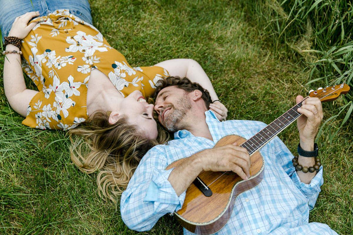 natürliches Portraitfoto eines verliebten Paares, das mit einer Gitarre auf der Wiese liegt