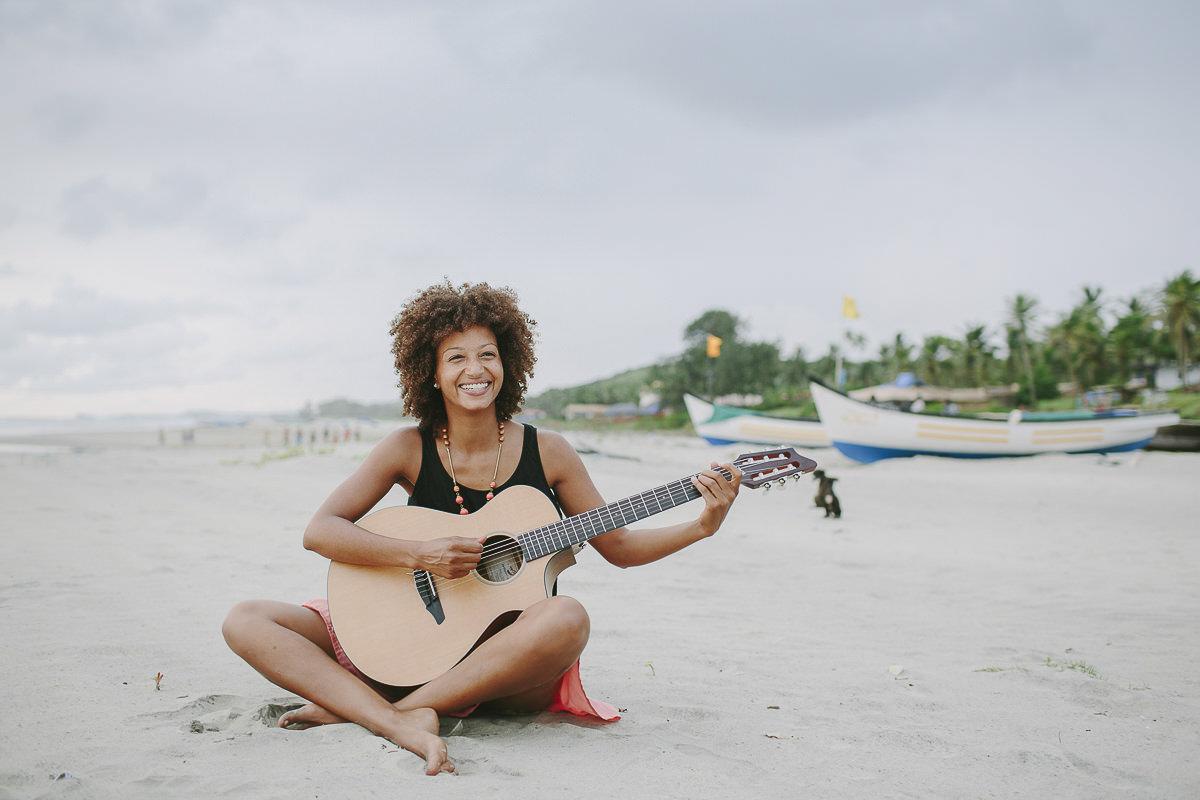 freundliches Portraitfoto einer lachenden Sängerin, die mit einer Gitarre am Strand sitzt