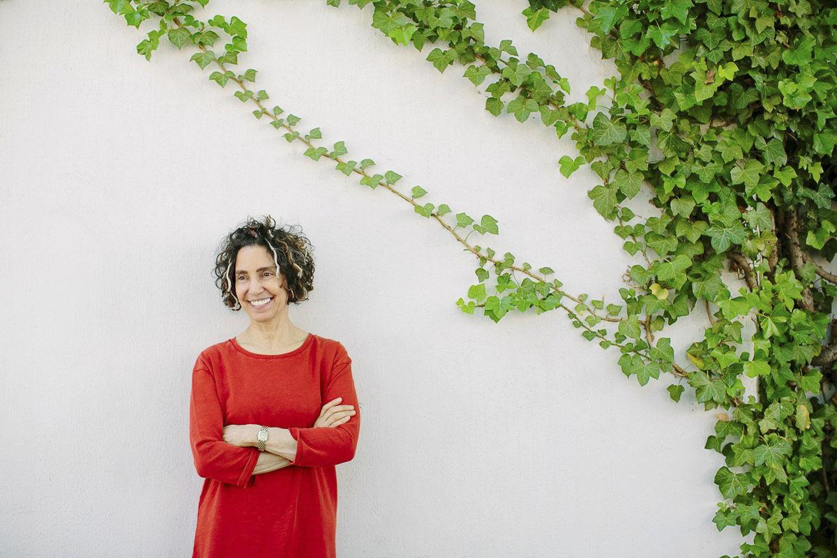 sympathisches Portraitfoto von Yoga Lehrerin Abby Galvin vor einer Wand mit Efeu