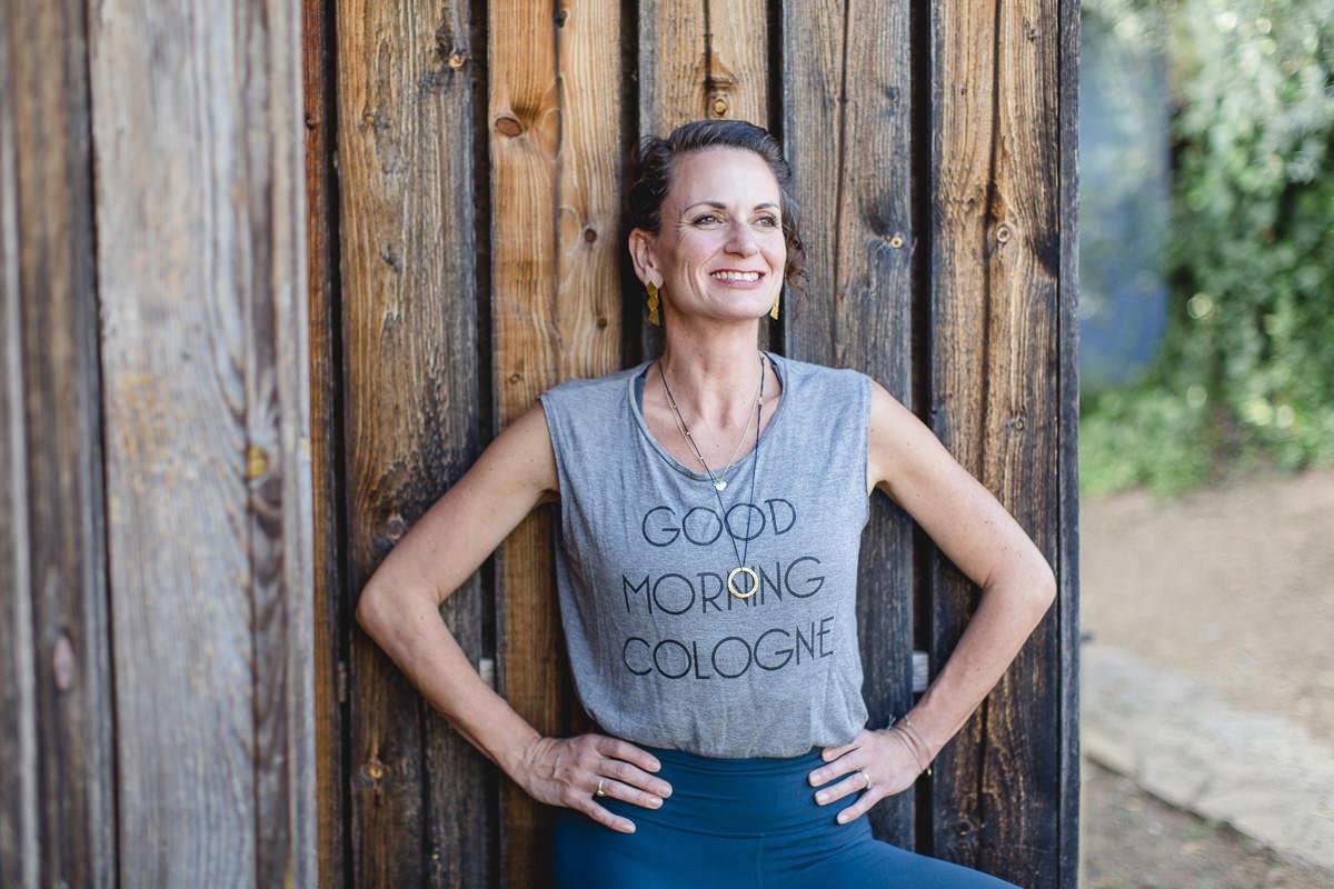 Portraitfoto von Yoga Lehrerin Nicole Bongartz vor einer Holzwand