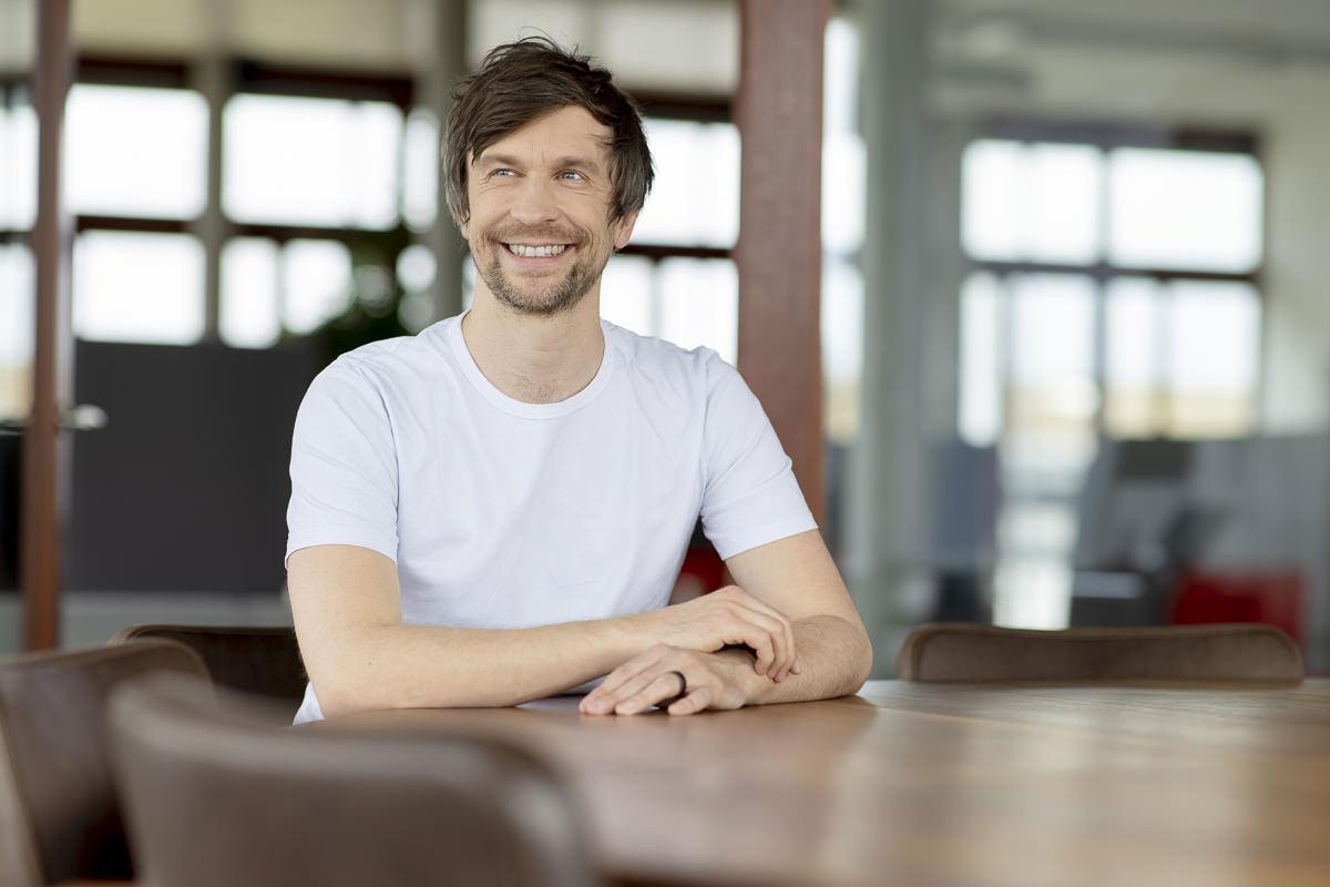 Portraitfoto Pose: Ein Mann sitzt an einem Konferenztisch und schaut zur Seite | Foto: Hanna Witte