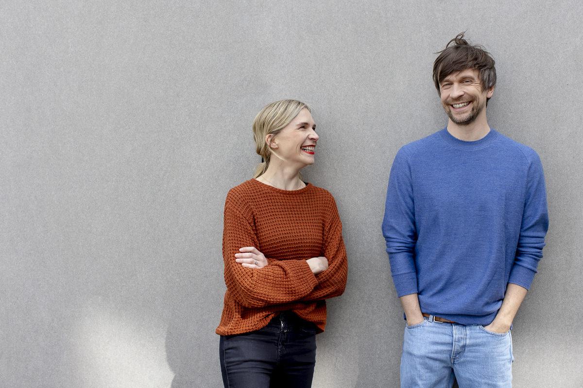 Arbeitskollegen lehnen an einer hellen Wand und lachen natürlich fürs Portraitfoto | Foto: Hanna Witte