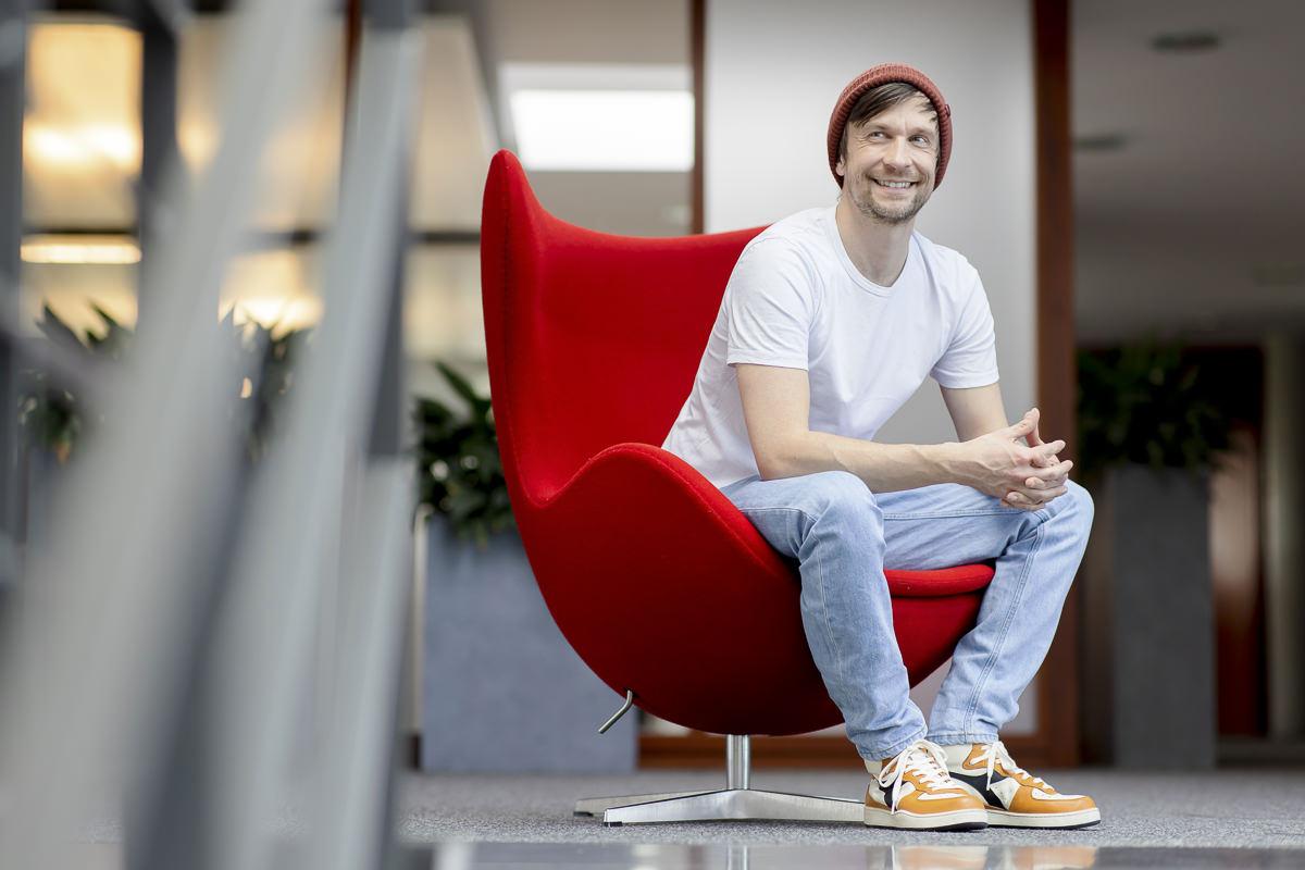ein Mann sitzt fürs Portraitfoto auf einem roten Designstuhl | Foto: Hanna Witte
