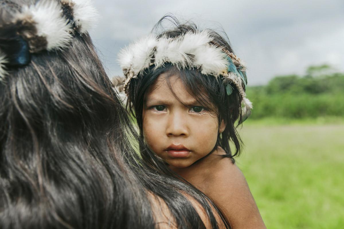 Portraitfoto von einem indigenen Kind mit Federschmuck | Foto: Hanna Witte