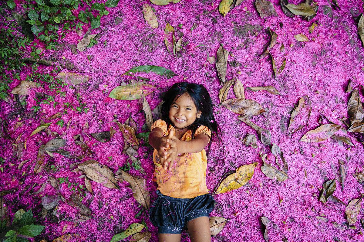 Foto von einem indigenen Mädchen, das auf lila Blumen liegt | Foto: Hanna Witte