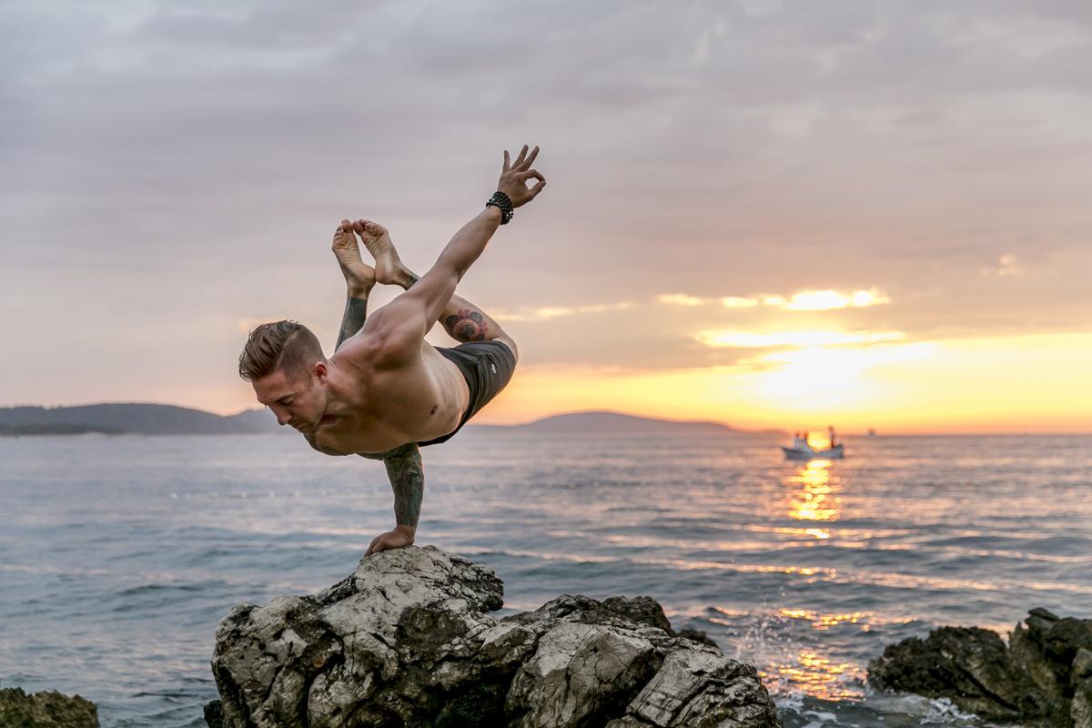 ein Mann macht ein Yoga Asana auf einer Hand am Meer von Kroatien | Foto: Hanna Witte