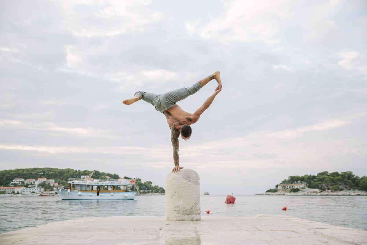 ein Yoga Lehrer macht ein Yoga Asana mit einer Hand auf einem Stein | Foto: Hanna Witte