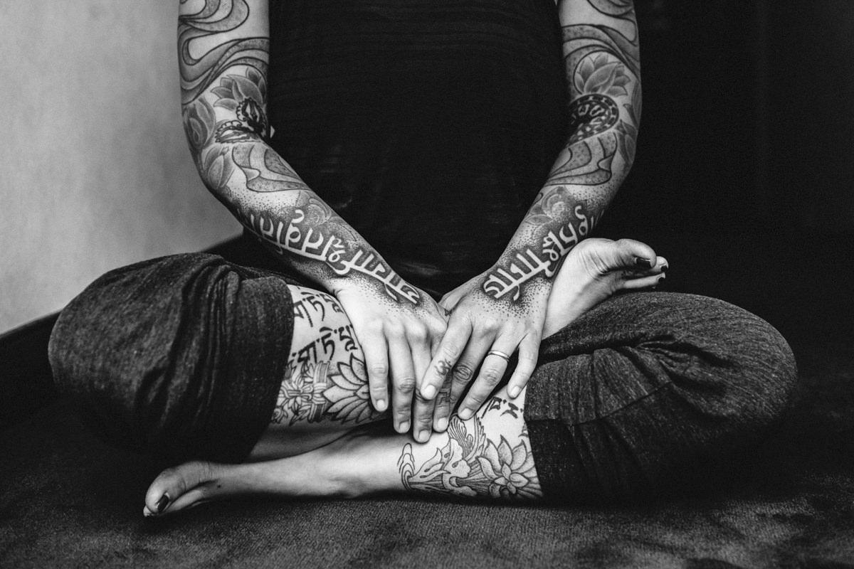 eine tätowierte Teilnehmerin der Yoga Conference sitzt im Schneidersitz | Foto: Hanna Witte
