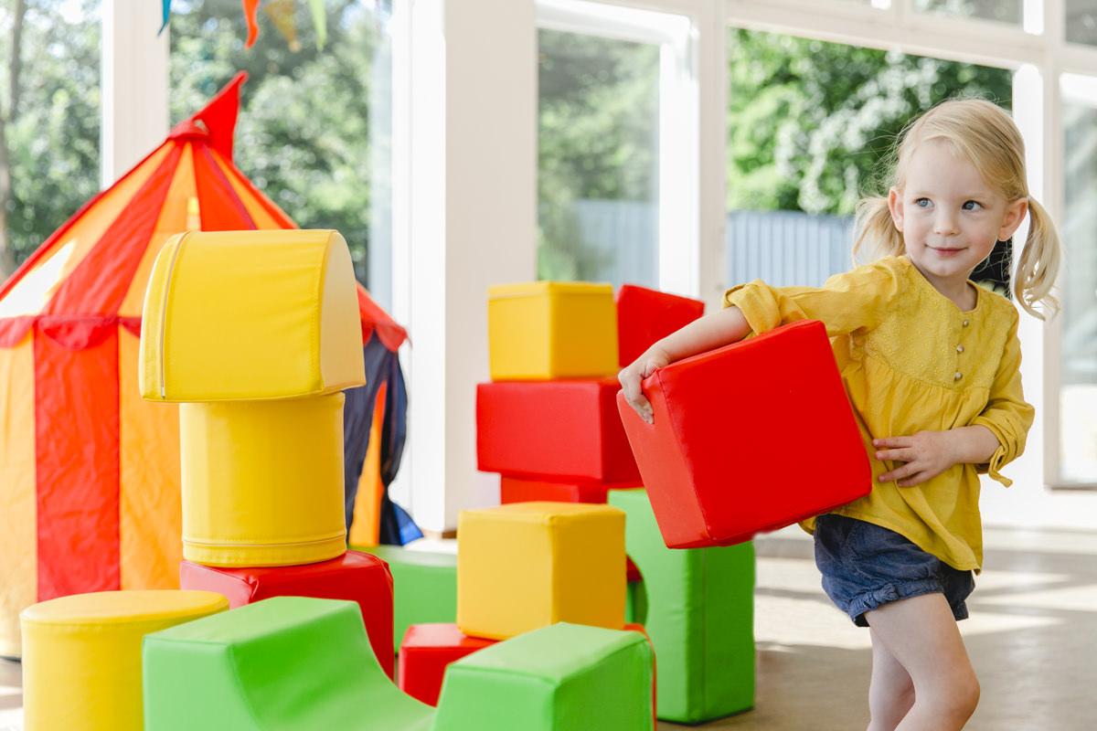Foto von einem Mädchen mit großen, bunten Bauklötzen | Foto: Hanna Witte