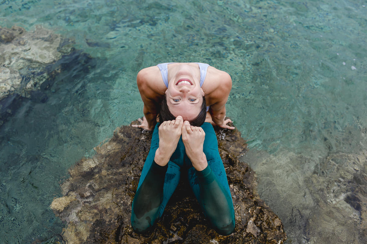 portrait of yoga teacher Mackenzie Miller doing yoga by the sea