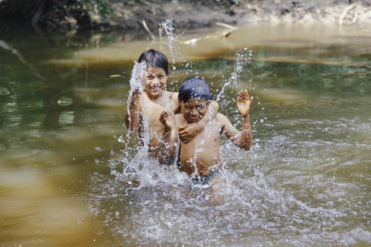 indigene Kinder spielen im Wasser des Amazonas in Ecuador | Foto von NGO Fotografin Hanna Witte