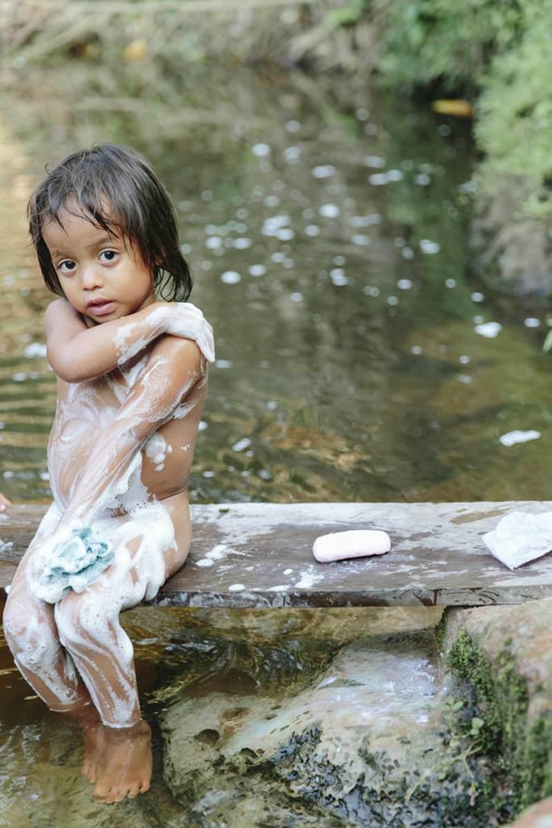ein indigenes Kind wäscht sich in einem Fluss in Ecuador | fotografiert von Hanna Witte
