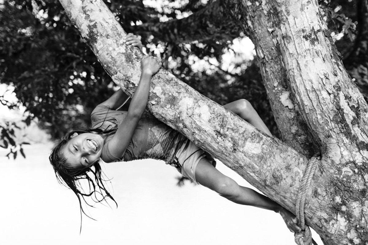 ein indigenes Mädchen klettert ausgelassen an einem Baum | Foto von NGO Fotografin Hanna Witte