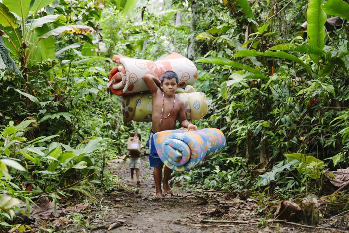 indigene Kinder helfen beim Entladen der Hilfsgüter für ihr Dorf in Ecuador | Foto von NGO Fotografin Hanna Witte