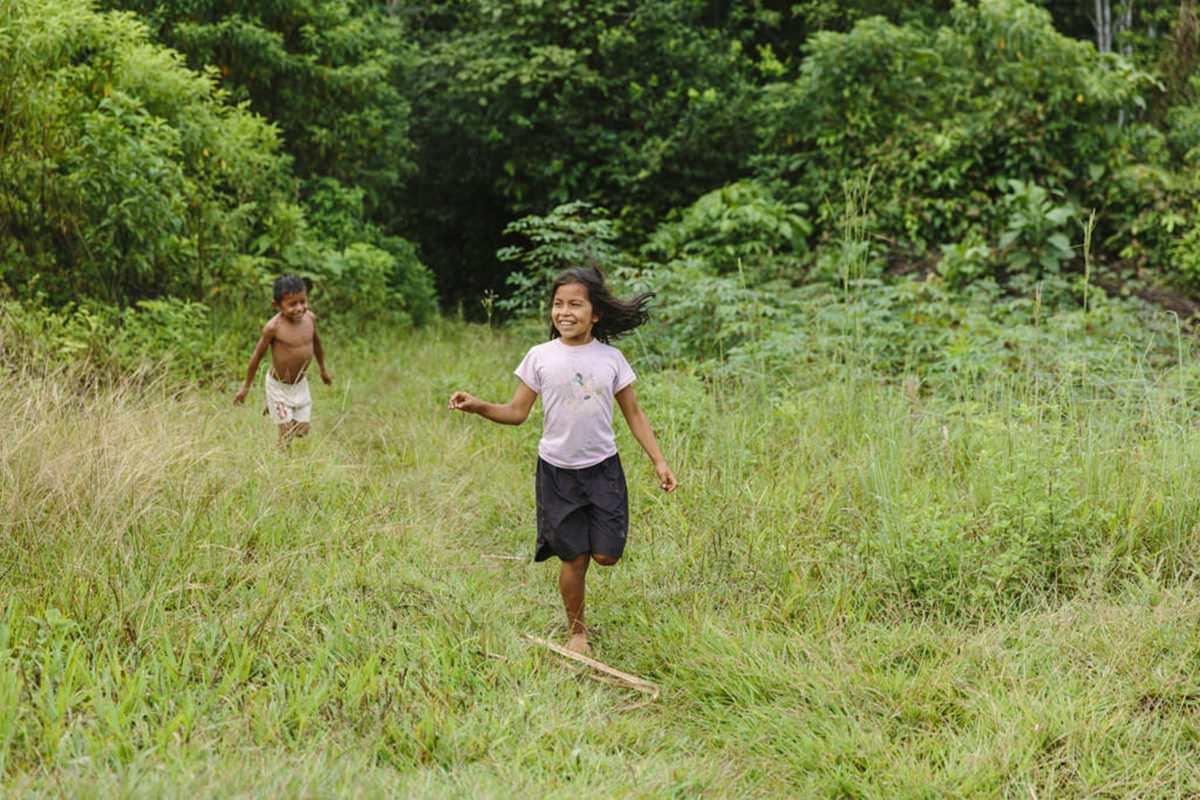 indigene Kinder laufen über eine Wiese im Regenwald von Ecuador | Foto von NGO Fotografin Hanna Witte