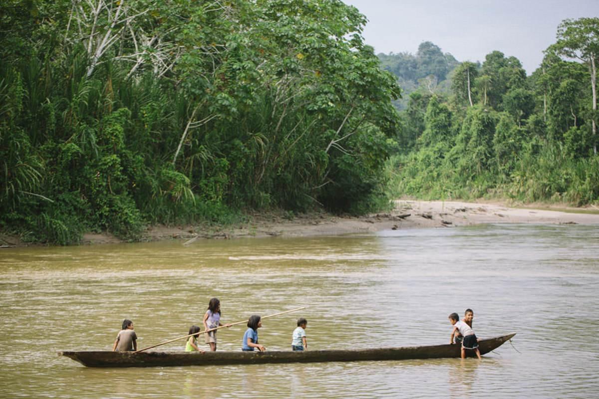 indigene Kinder fahren mit einem langen Boot über einen Fluss in Ecuador | Foto von NGO Fotografin Hanna Witte