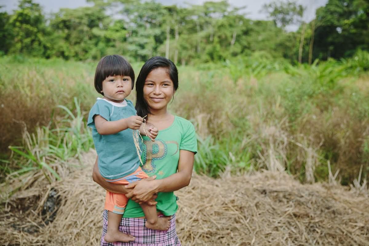 ein indigenes Mädchen trägt ihre Schwester auf dem Arm | Foto von NGO Fotografin Hanna Witte