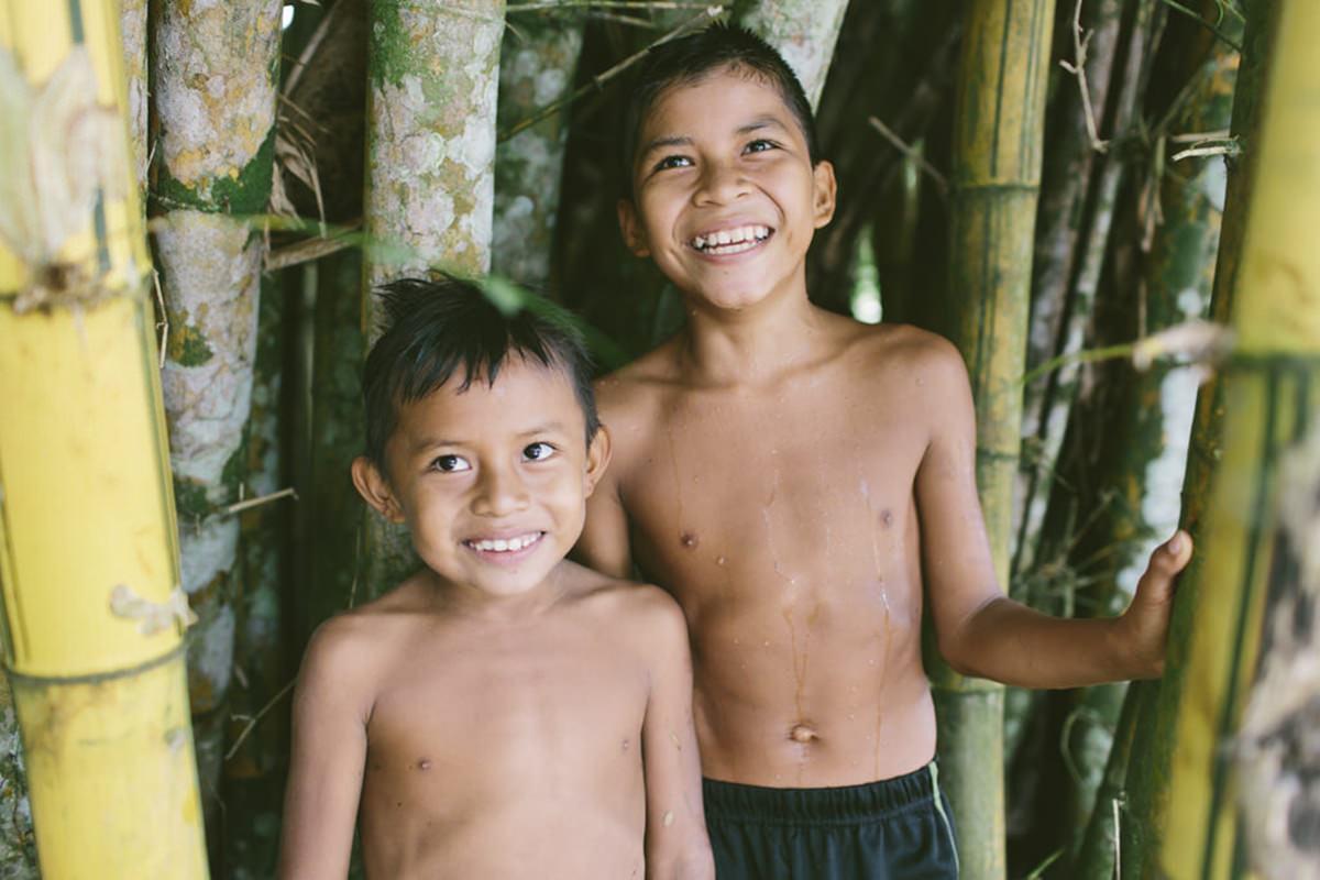 zwei indigene Kinder stehen zwischen dicken Bambusstangen| Foto von NGO Fotografin Hanna Witte