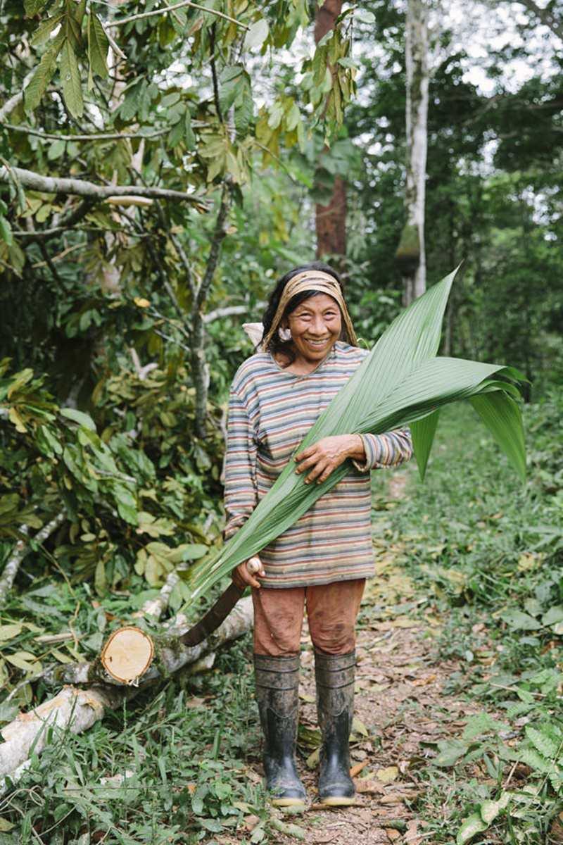 eine indigene Frau trägt große Palmblätter | Foto von NGO Fotografin Hanna Witte