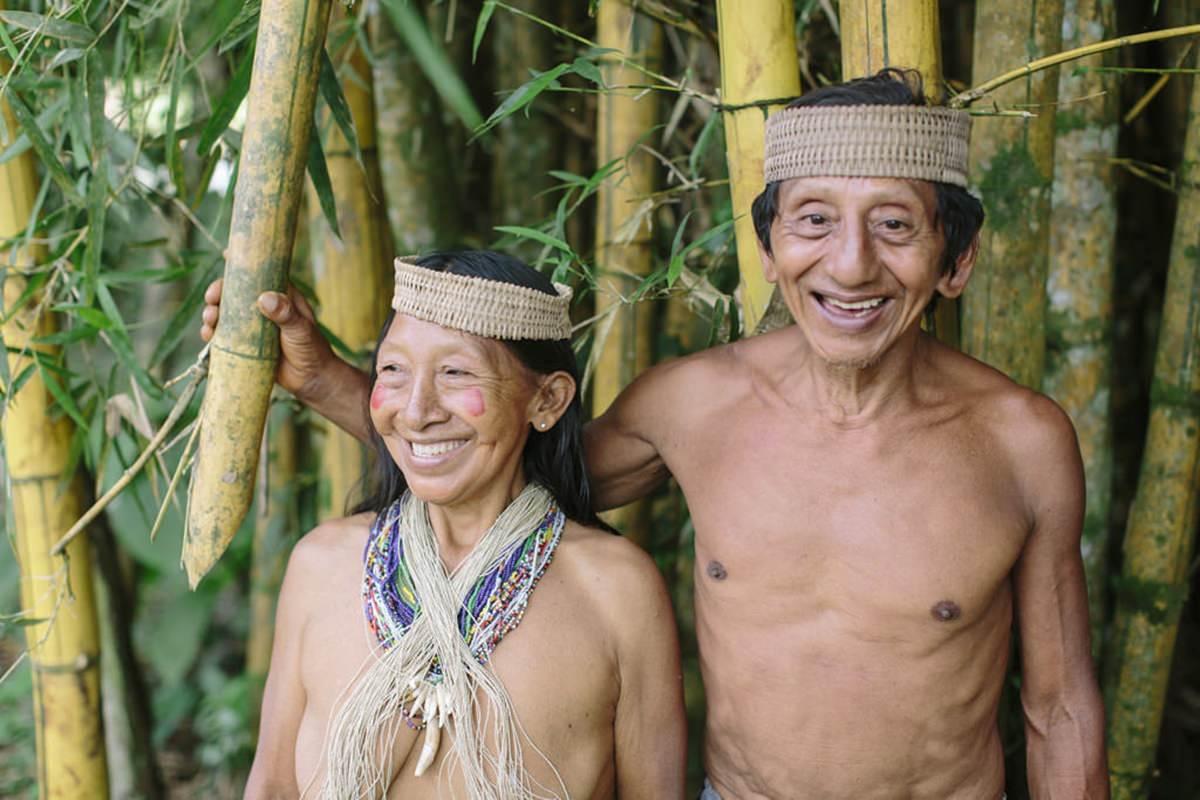 ein indigener Mann steht mit seiner Frau vor hohen Bambusstangen in ihrem Dorf in Ecuador | Foto von NGO Fotografin Hanna Witte