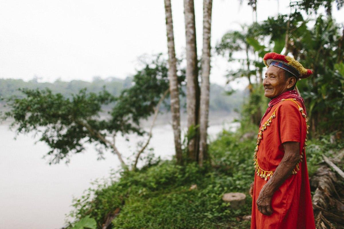ein indigener Mann in traditionellem Gewand steht am Amazonas in Ecuador | Foto von NGO Fotografin Hanna Witte