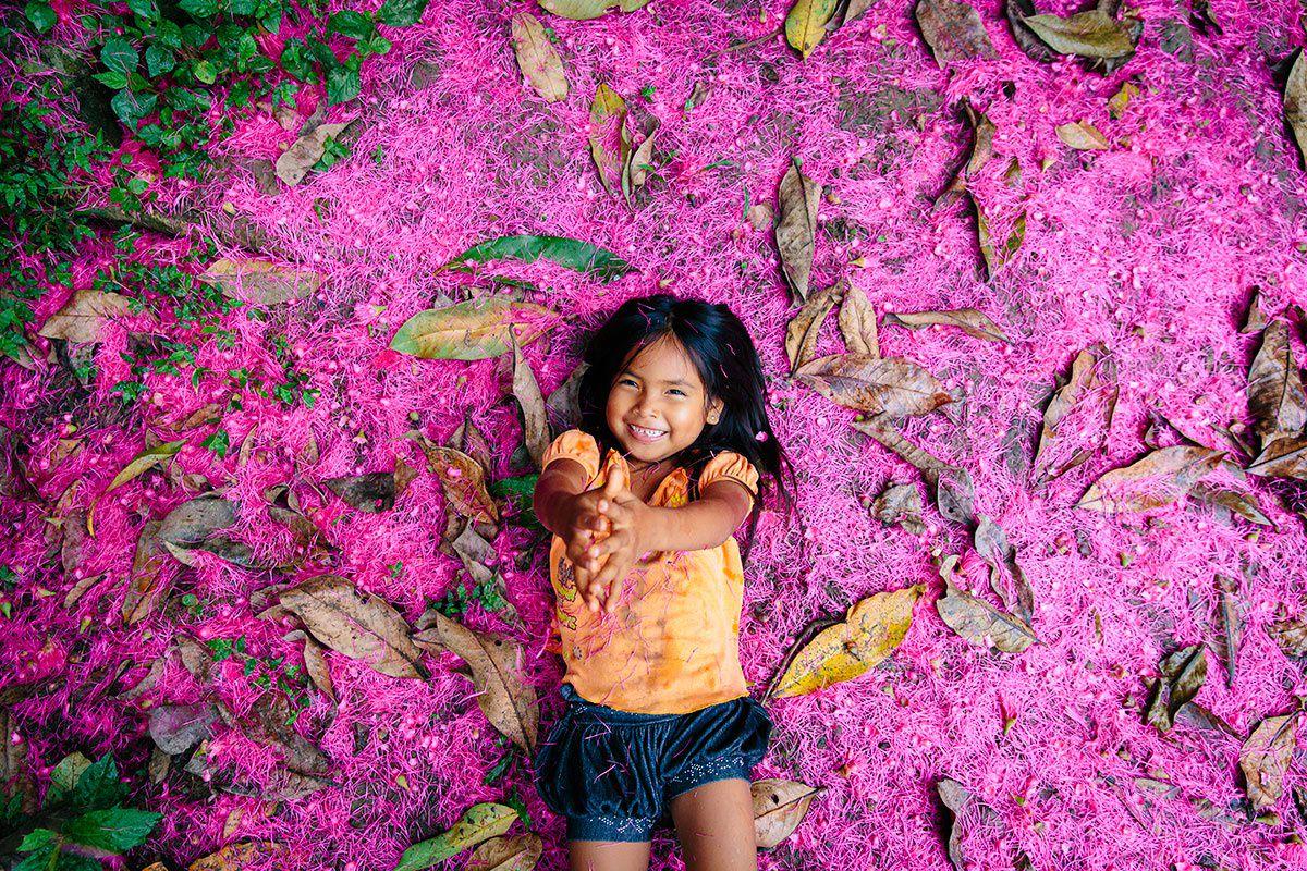 ein indigenes Mädchen liegt auf lilafarbenen Blüten im Regenwald von Ecuador | Foto von NGO Fotografin Hanna Witte