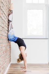 Foto von Yogalehrerin Alexandra Harfield, die eine Yoga Übung an der Wand macht