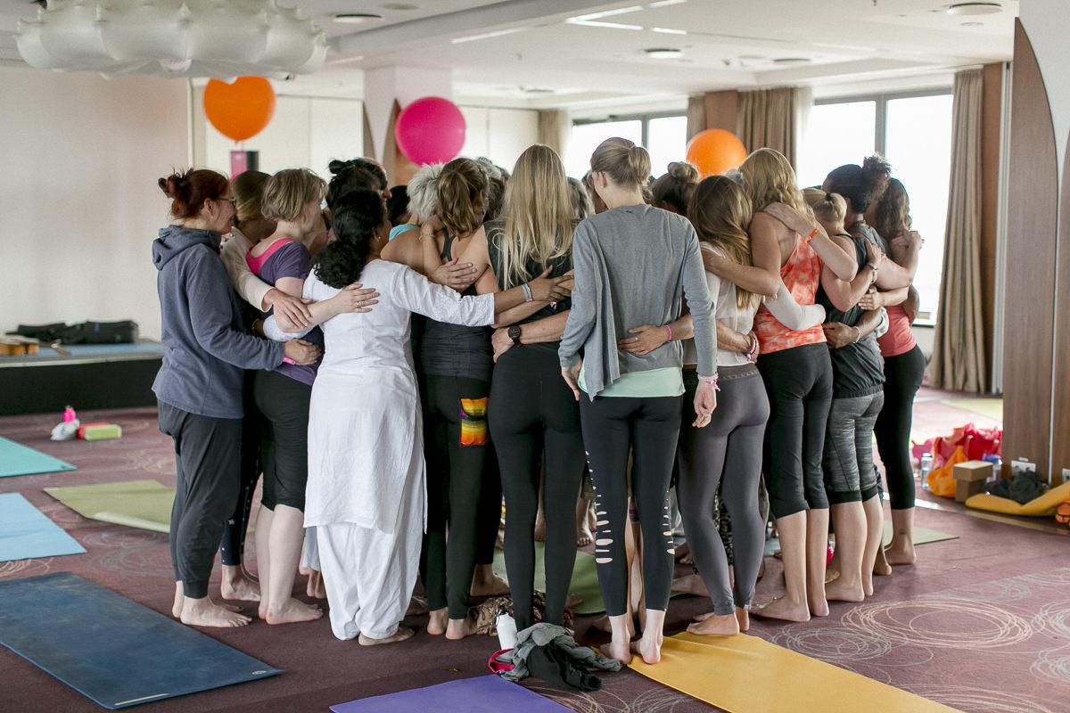 Teilnehmer der Yoga Conference Germany umarmen sich in einem Kreis
