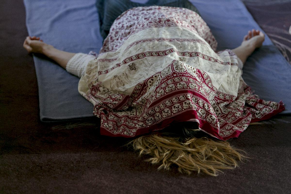 eine Teilnehmerin der Yoga Conference Germany 2018 entspannt sich mit einem Tuch über dem Gesicht