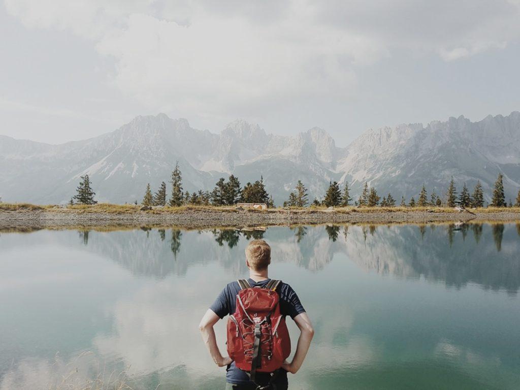Foto von einem Mann vor wunderschöner Naturkulisse mit einem See, Bäumen und Bergen