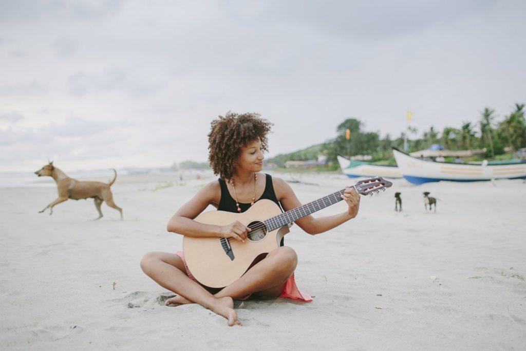 Foto von einer Musikerin mit Gitarre am Strand von Goa | Foto: Hanna Witte