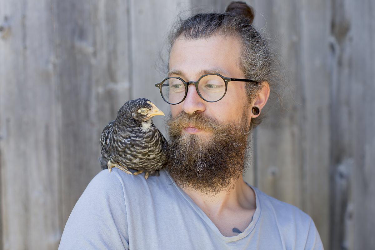 Portraitfoto von Roland Jensch mit Huhn auf seiner Farm in Kanada