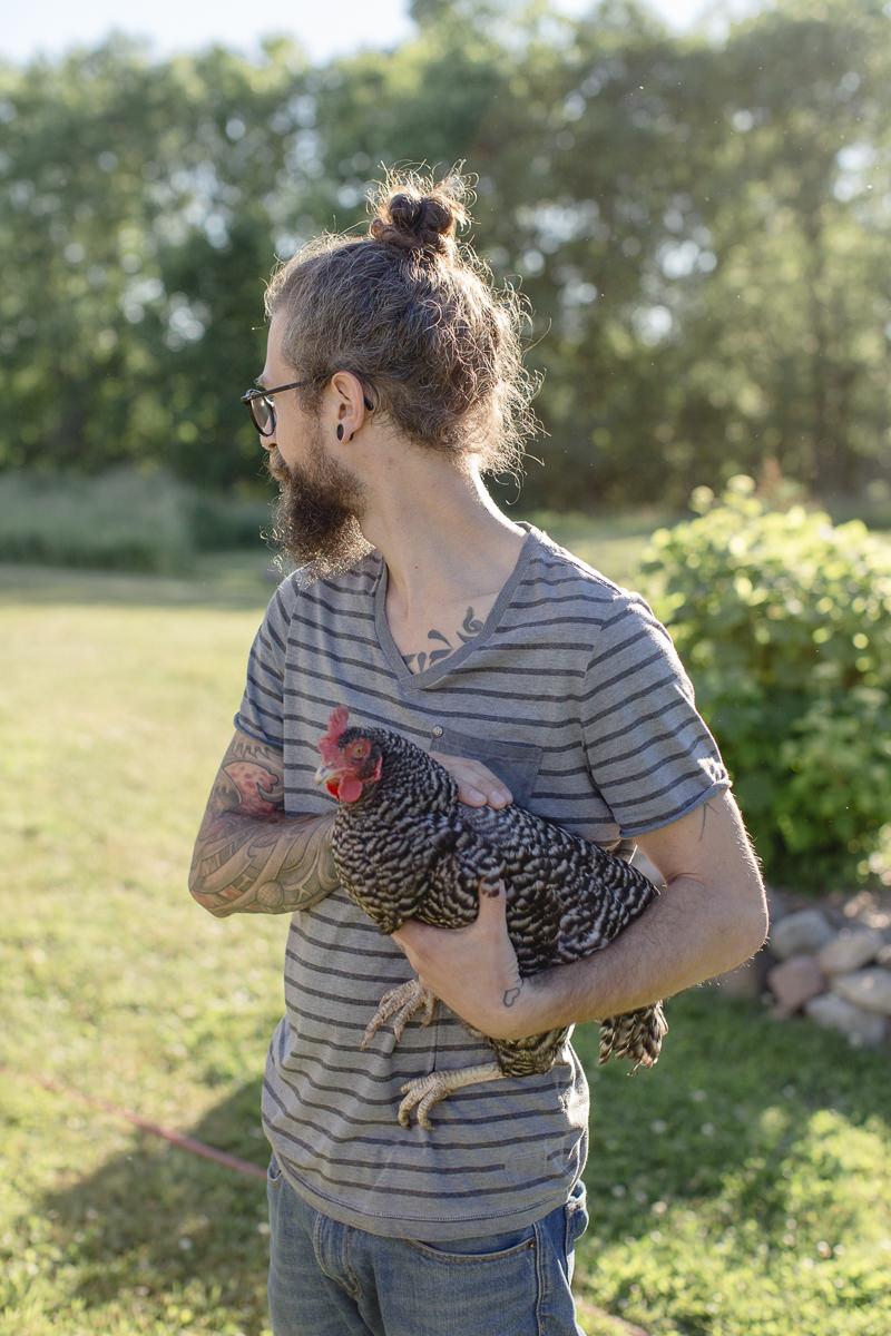 Portrait von Roland Jensch mit Huhn für die Fotoreportage auf seiner Farm in Kanada